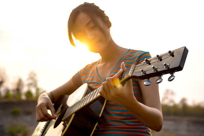 young-womans-hand-playing-guitar-outdoors