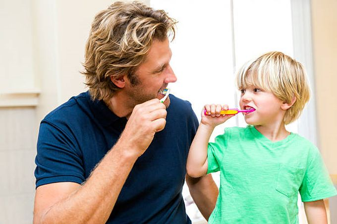 father-and-son-brushing-teeth-together