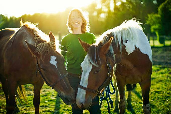 young-woman-with-horses-in-pasture