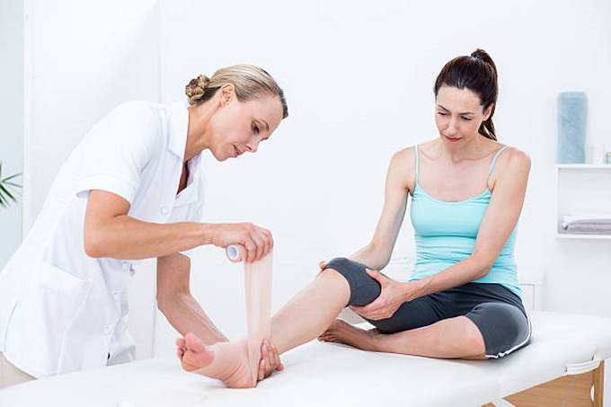 doctor-bandaging-her-patient-ankle