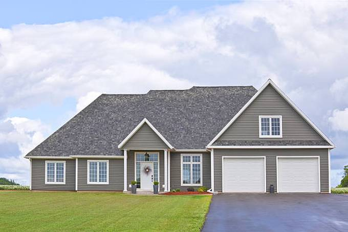 exterior-of-a-gray-country-home-with-a-manicured-lawn