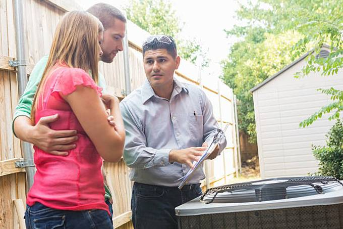 air-conditioner-repairman-explaining-cost-of-repairs-to-homeowners